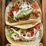 Soft tacos in a row on a wooden board | | New Jersey mexican restaurants | foodwithaview.com
