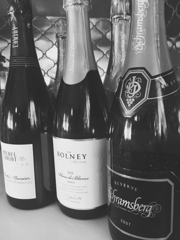 Bottles of sparkling wine and champagne in a row | Sparkling wine and champagne guide on foodwithaview.com