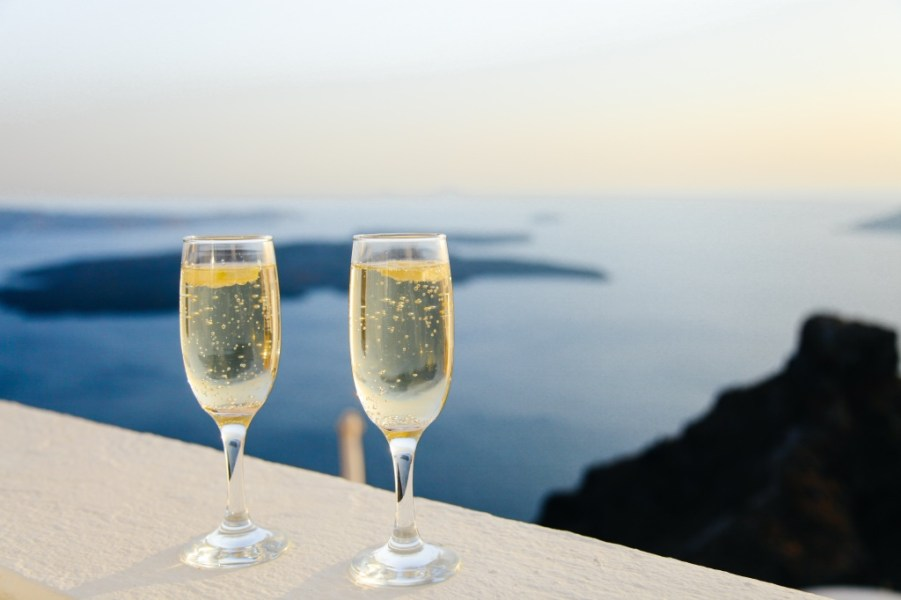 Two champagne glasses with a beautiful water view | Guide to champagne and sparkling wine on foodwithaview.com