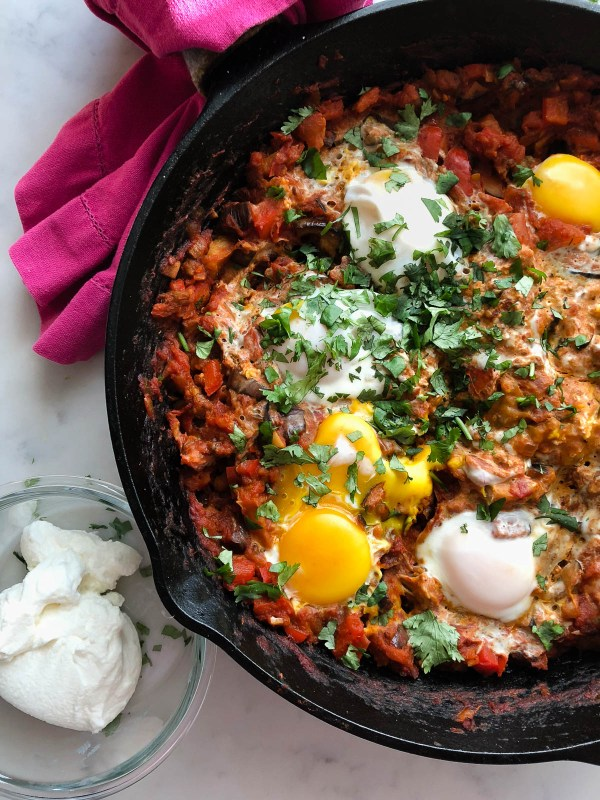 Shakshuka in a cast iron pan with homemade labneh | Jerusalem: A Cookbook Review | foodwithaview.com