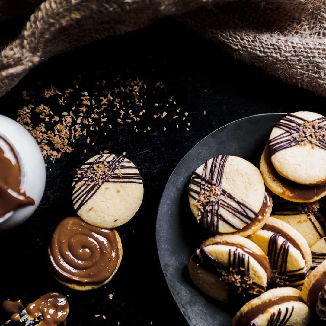 A plate full of Billionaire Alfajores with Toasted Coconut and a thick swirl of Dulce de Leche