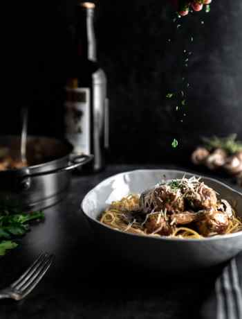A sprinkle of parsley falling over chicken marsala meatballs