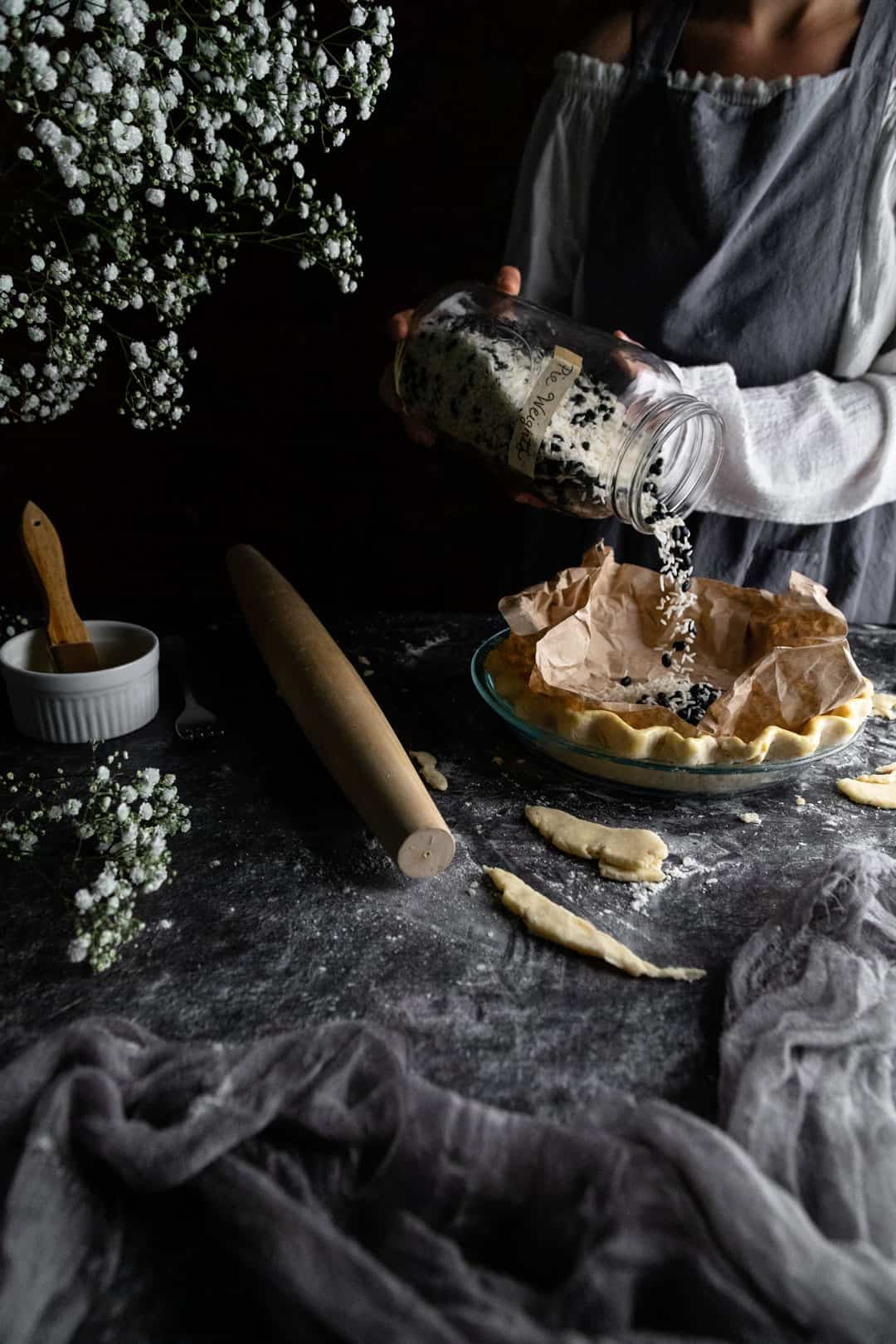 Pouring rice and bean pie weights into a buttery pie crust