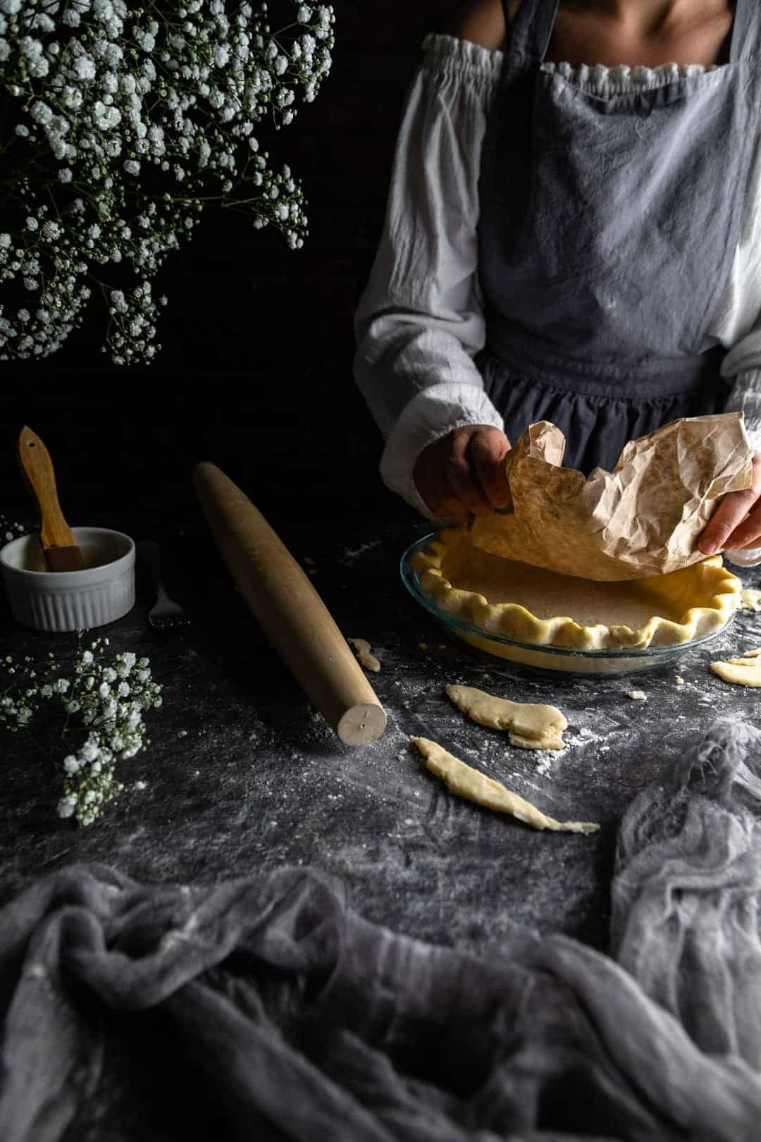 A woman placing a crumpled coffee filter into the bottom of an unbaked crimped pie crust next to a rolling pin and vase of tiny white flowers