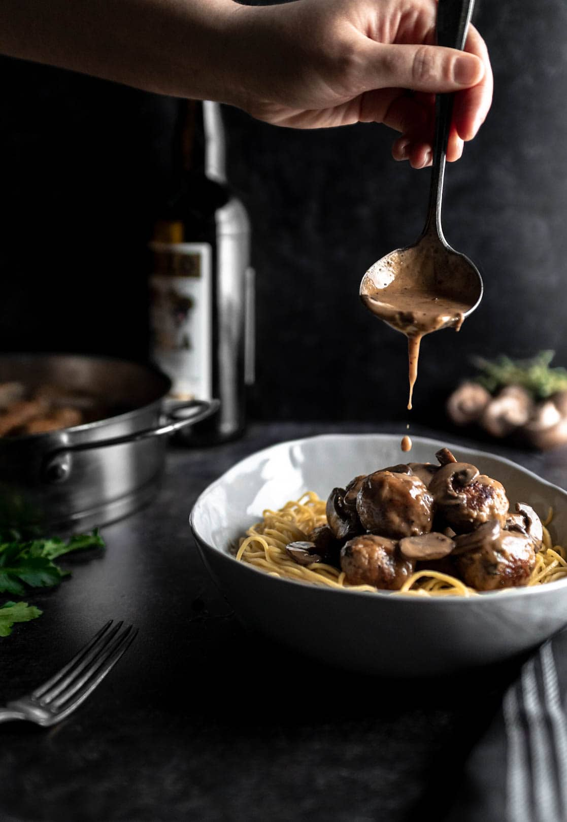 a ladle pouring creamy marsala sauce over a bowl filled with spaghetti and Chicken Marsala Meatballs