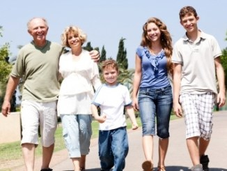 Ant-aging ingredients should be used by all, whatever their age. Family walking arm in arm along a road towards the camera and of all ages.