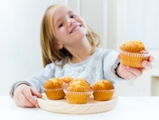 Beautiful little girl offering the viewer a small cupcake.