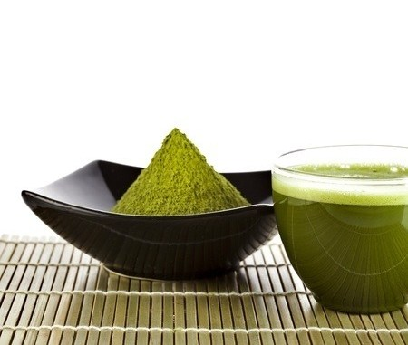 Green tea in a black bowl with a clear glass cup of the beverage next to it.