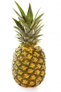 Pineapple, fully ripe and sitting on a white background.