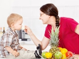 A child being presented with some food on a spoon by his mother.