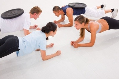 Fit people doing press-ups on the gym floor.
