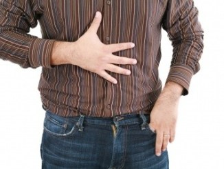 A man feeling the front of his stomach.