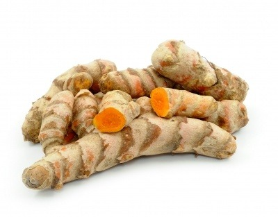 Turmeric rhizomes, some cut in half to show their orange colour on a white background.