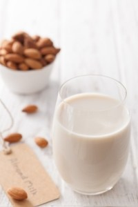 Almond milk in a glass, with almonds in a bowl.