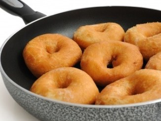 Ring doughnuts in a black frying pan.