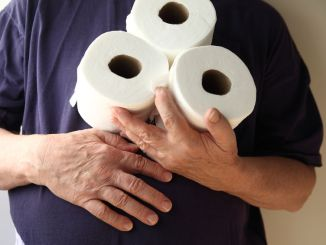Man with hand over his stomach holds three rolls of toilet paper. A symptom of gastroenteritis and inflammatory bowel disease.