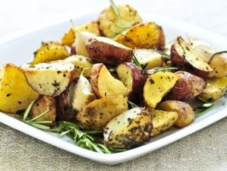 A white dish with rasted potatoes and various herbs.