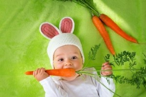 Baby in rabbit hat eating fresh carrot. Copyright: candy18 / 123RF Stock Photo