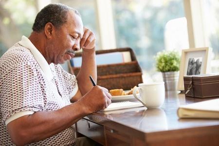 Senior man writing memoirs in book sitting at desk.