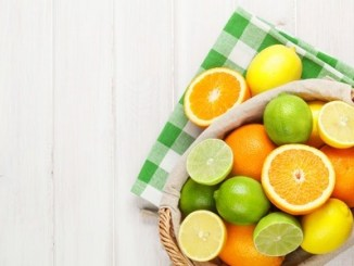 Various citrus fruit in a basket on a white table.