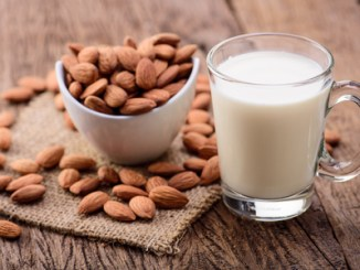 Almonds in a white bowl, almond milk in a glass with handle on a wooden table.