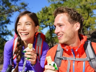 Outdoors couple eating muesli bar hiking. Happy people enjoying granola cereal bars living healthy active lifestyle in mountain nature. Woman and man hiker sitting laughing during hike.