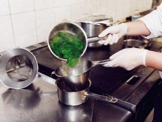 Chef pouring spinach through a sieve after blanching.