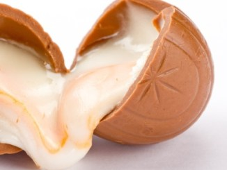 Creme eggs: A broken creme egg with the fondant icing oozing out of both ends. All on a white background.
