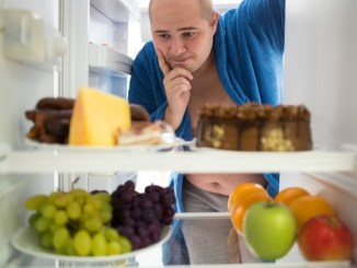 Corpulent man contemplating unhealthy food rather than healthy food