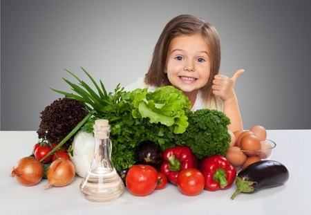 A little gitl giving the thumbs up behind a load of vegetables.