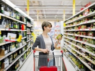 Pretty woman with a cart shopping and choosing goods at the supermarket. Healthy food.
