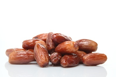 Photograph of sugar covered and dried dates (deglet noor sub-type) palm fruits on white with a natural reflection. the fruit is also known as phoenix dactylifera.