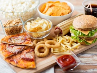 55283534 - fast food and unhealthy eating concept - close up of fast food snacks and cola drink on wooden table