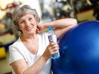 portrait of aged woman with bottle of water by blue ball