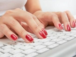 Beautiful nails typing on a keyboard.