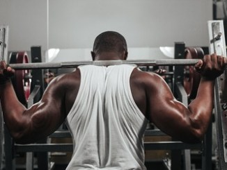 43776533 - weight training african doing bodybuilding in gym