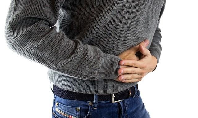 Man in grey jumper clutching stomach or abdomen. Photo shows mid -part of body, no head. Could he be suffering with IBS, diarrhea/diarrhoea or constipation.