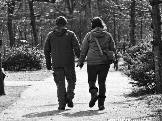 A couple walking hand in hand down a country path. Betaine may help them in this health.