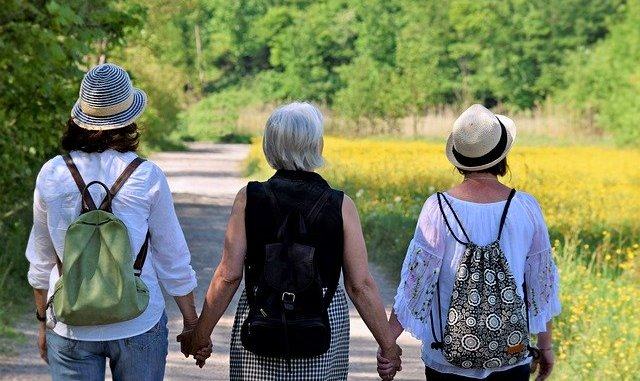 Three friends from the back walking down a lane. have all three experienced the menopause yet ?