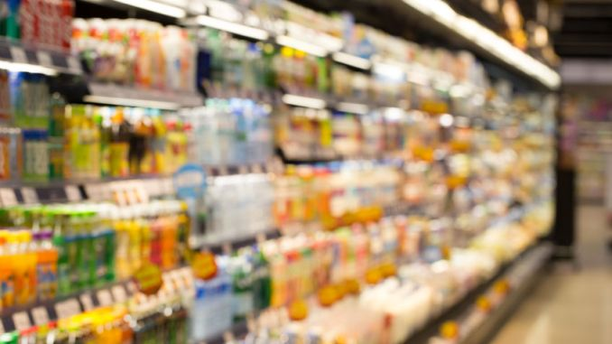 Supermarket, blur view of beverage product on refrigerator shelves in supermarket. Look out for foods treated by high pressure processing.