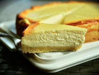 Cheesecake slice on a spoon, taken from a tart.