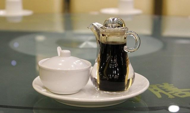 Soy sauce in a bottle with spout and a jar of soy paste.