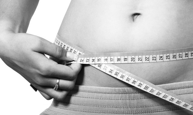 A belly with a woman measuring her waistline.. In black and white.