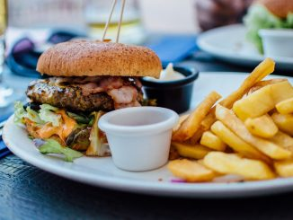 Burger and chips, jar of mayonnaise all on a white plate. Unhealthy eating may be the root cause of sepsis.