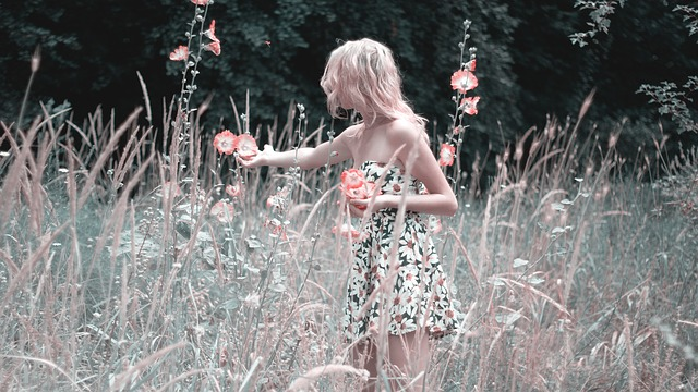Girl collecting flowers in a meadow.