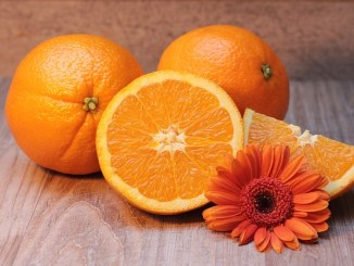 Oranges with an orange gerbera on a table as a source of vitamin C.. One of the top foods for tackling diabetes.
