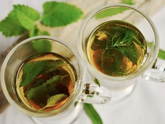Peppermint tea leaves in two glass cups on a atble with some free green leaves.