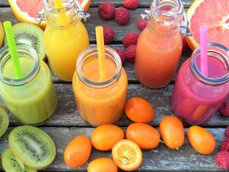 Smoothies in different colours on a board. An example of diet drinks with various fruits surrounding the glasses.