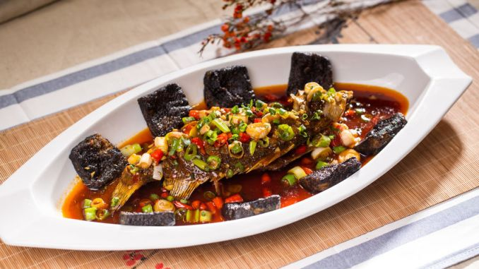 Stinky mandarin fish with stinky tofu in a white dish.