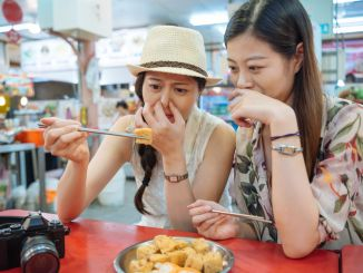 two teenage chinese girls trying stinky tofu. They hold their noses.